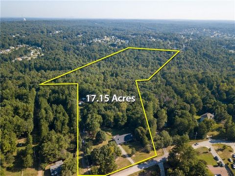 Located in Flowery Branch. A total of 17 acres which includes a 3 bed/2 bath home, carport and creek located in Flowery Branch! Home boasts exposed beams in the living area, hardwood floors, master on the main, wood fireplace and basement with a work...