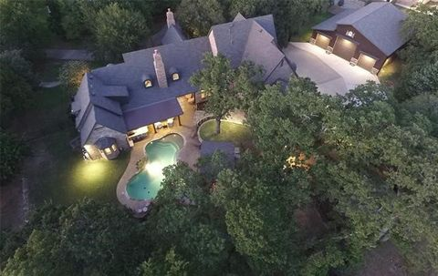 Exclusive 2 Acre Estate Nestled in the Wooded Cross Timbers Area of Flower Mound. Circular Driveway & Gated Motor Court surrounded by 3 Separate Garages capable of housing 16 vehicles with air conditioned 50X45 RV Storage. Custom Wood Beams, Arched W...